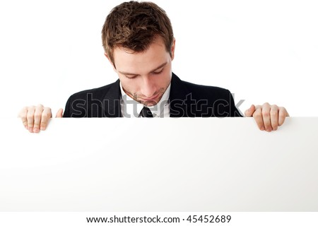 Portrait of young man looking down at blank sign. Isolated on white.