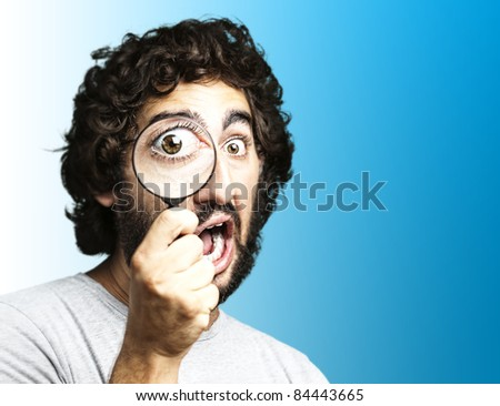 portrait of young man looking through a magnifying glass against a blue background