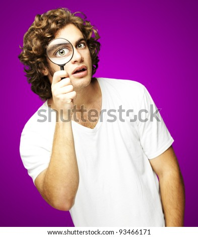 portrait of young man looking through a magnifying glass against a pink background