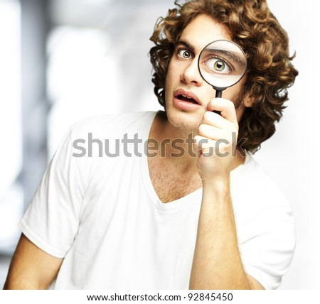 portrait of young man looking through a magnifying glass indoor