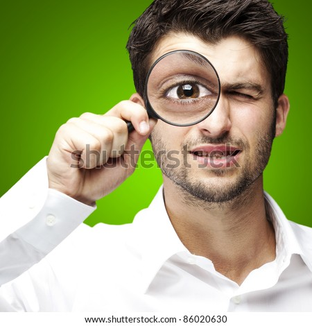 portrait of young man looking through a magnifying glass over green background