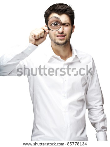 portrait of young man looking through a magnifying glass over white background