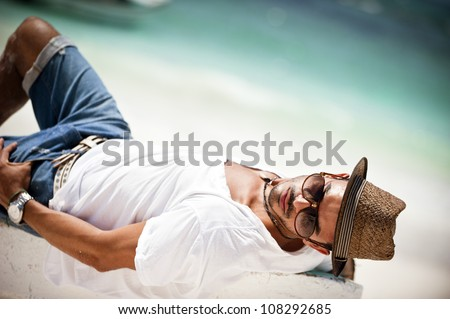 Portrait of young man lying on a boat on tropical beach
