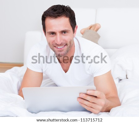 Portrait Of Young Man Lying On Bed Using Laptop, Indoors