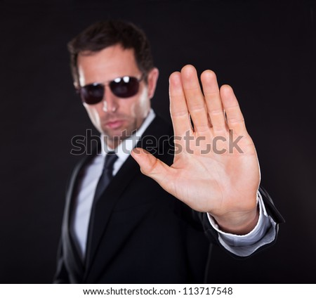 Portrait Of Young Man Making Stop Gesture Isolated On Black Background
