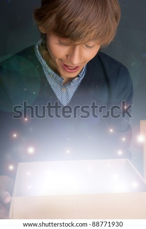 Portrait of young man opening gift box. He is happy. Magical shine inside box