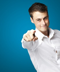 portrait of young man pointing with finger against a blue background