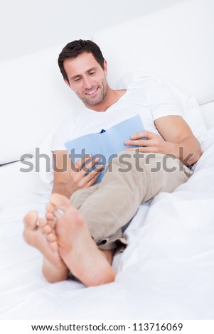 Portrait Of Young Man Reading Book On Bed, Indoors