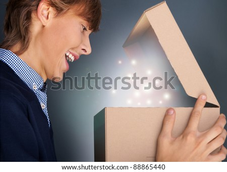 Portrait of young man received christmas gift. He opened gift box and discovered a miracle. Shining glitter in the box