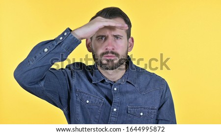 Portrait of Young Man Searching for Opportunities, Yellow Background