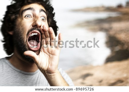 portrait of young man shouting against a beach background