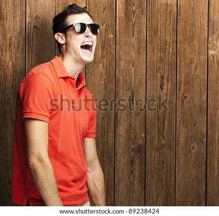 portrait of young man shouting and joking against a wooden wall