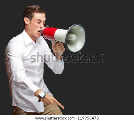 Portrait Of Young Man Shouting On Megaphone Isolated On Black Background