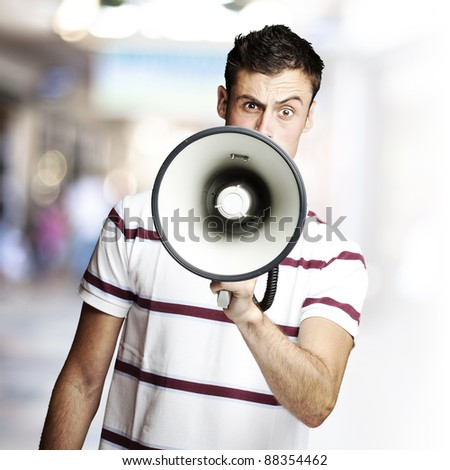portrait of young man shouting using megaphone against a crowded place - stock photo