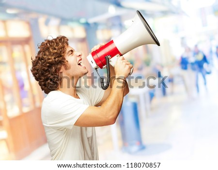 Portrait Of Young Man Shouting With A Megaphone, Indoor