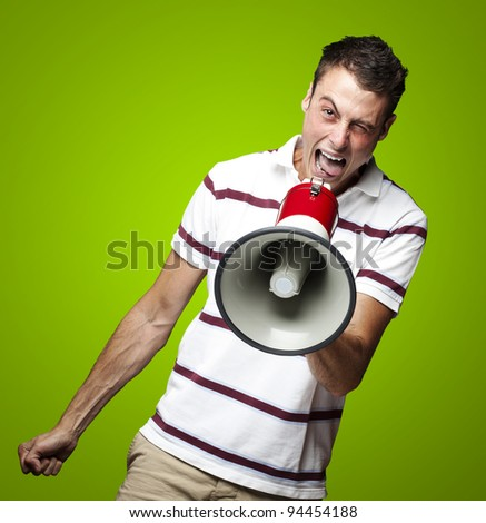 portrait of young man shouting with megaphone against a green background