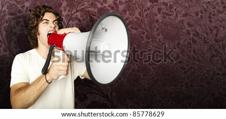 portrait of young man shouting with megaphone against a grunge background