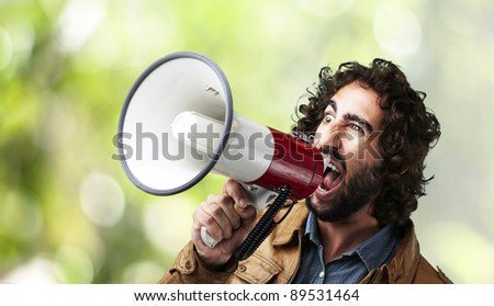 portrait of young man shouting with megaphone against a nature  background