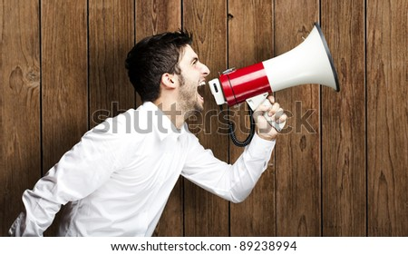 portrait of young man shouting with megaphone against a wooden wall