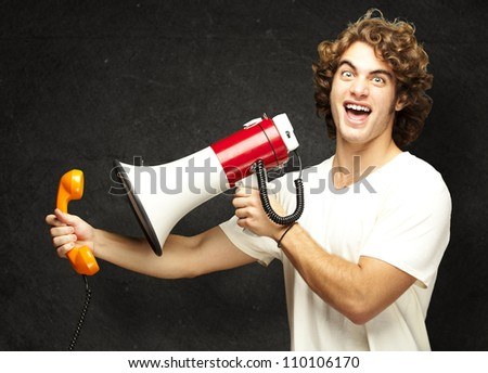 portrait of young man shouting with megaphone and talking on vintage telephone against a grunge wall