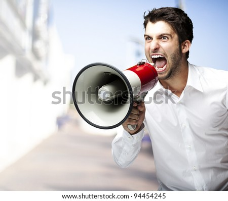 portrait of young man shouting with megaphone at street - stock photo