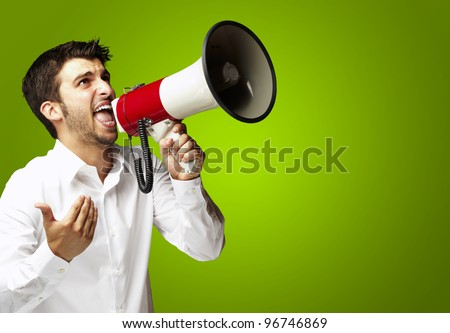 portrait of young man shouting with megaphone over green background