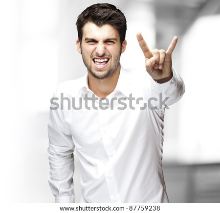 portrait of young man singing and doing rock and roll symbol indoor