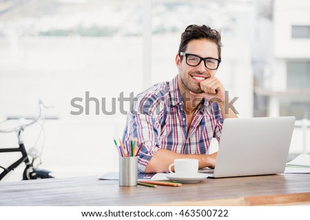 Portrait of young man sitting at his desk in the office #463500722