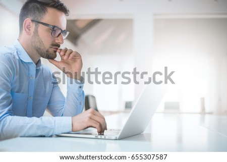 Portrait of young man sitting at his desk in the office #655307587
