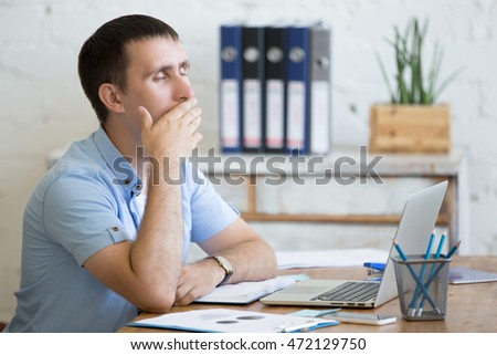 Portrait of young man sitting at the table in front of laptop, sleepy, tired, overworked or lazy to work. Attractive business man yawning in home office relaxing or bored after work on laptop computer #472129750
