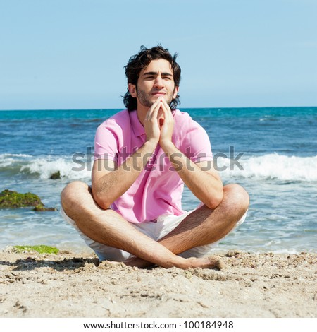 Portrait of young man sitting in lotus pose on sand on beach and meditating. Mediterranean sea at background
