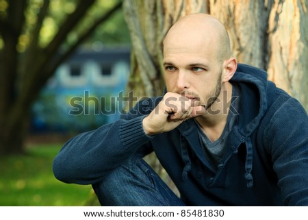 Portrait of young man sitting in park and thinking - stock photo