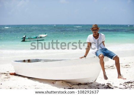 Portrait of young man sitting on a boat on tropical beach