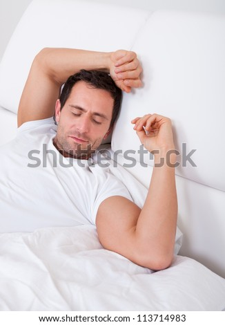 Portrait Of Young Man Sleeping On Bed In Bedroom - stock photo