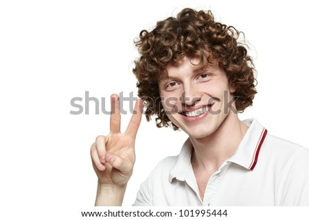 Portrait of young man smiling and showing you victory sign on white background - stock photo