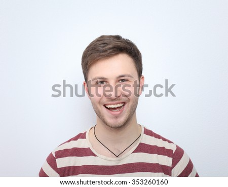 Portrait of young man smiling isolated on gray background - Shutterstock ID 353260160