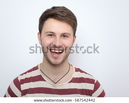Portrait of young man smiling isolated on gray background - Shutterstock ID 587542442