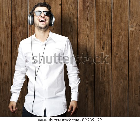 portrait of young man smiling wearing sunglasses against a wooden wall
