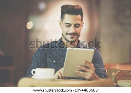 Portrait of young man smiling while using tablet at cafe #1094488688