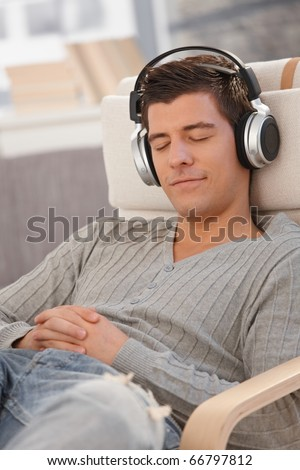 Portrait of young man smiling with eyes closed, listening to music via headphones at home.?