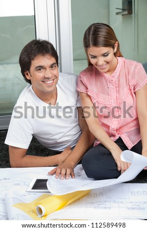 Portrait of young man smiling with woman looking at house plans