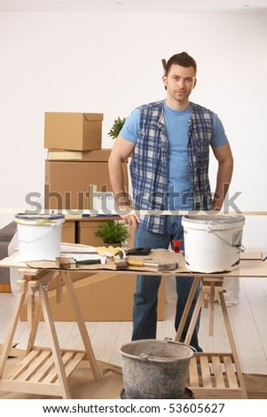 Portrait of young man standing at table in new house, preparing to paint walls.
