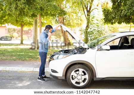 Portrait of young man standing in front of his broken car, looking at car engine and talking on cell phone