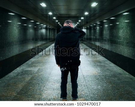 portrait of young man standing in the tunnel, blurred lights #1029470017