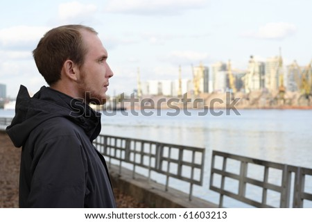 portrait of young man standing on river embankment and looking into the distance