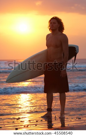 Portrait of young man standing on seashore with windsurf board at sunset