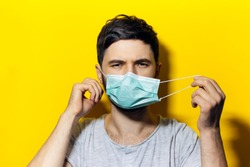 Portrait of young man, takes off the medical flu mask, on background of yellow color.