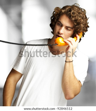 portrait of young man talking on a vintage telephone indoor