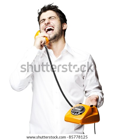 portrait of young man talking using vintage telephone laughing over white background
