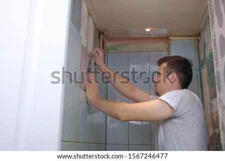 Portrait of young man tiler making renovation repair at home, removes tiles from wall in toilet by hands. Construction repairing manual works.